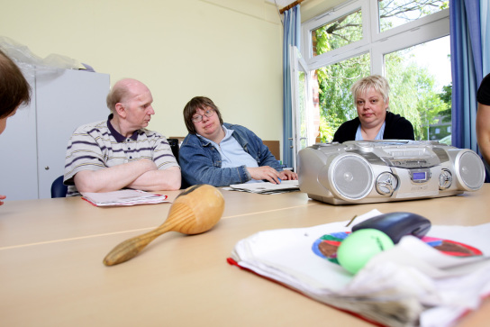 drei Mitarbeiter der Musik AG sitzen um einen Tisc