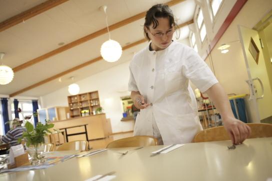 eine Mitarbeiterin deckt die Tische im Speisesaal