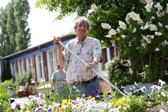 ein Gärtner bei der Pflege eines üppigen Blumenb