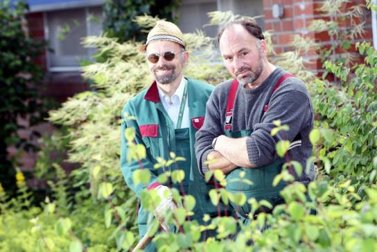 zwei Gärtner umgeben von grünen und blühenden S