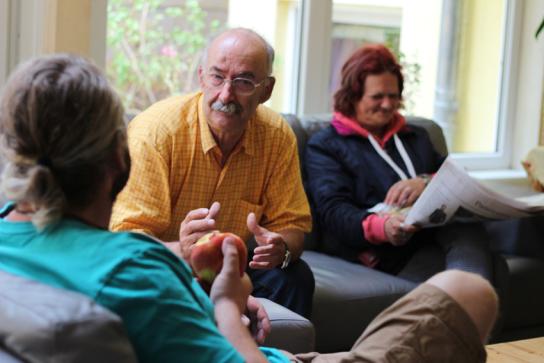 Bewohner sitzen im Wohnzimmer und diskutieren.