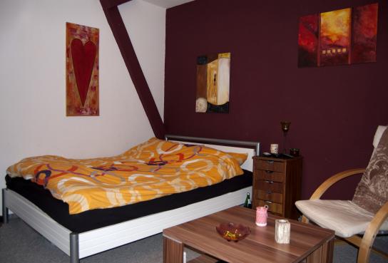 Hier ist ein Einzelzimmer unserer WG Lohbarbek zu sehen. In dem Zimmer steht ein Bett, ein Tisch, ein kleiner Schrank und ein Stuhl.