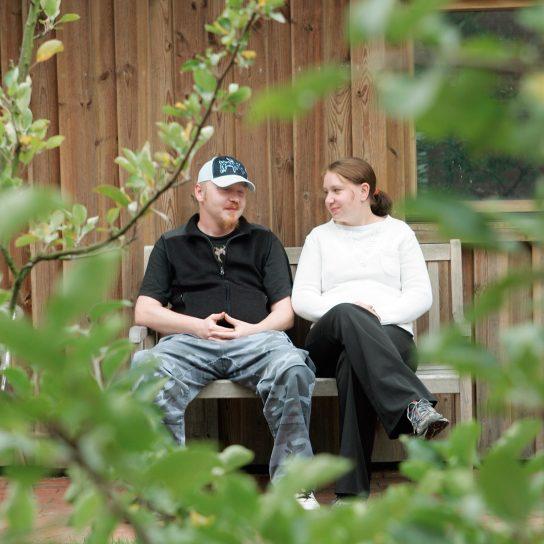Eine Frau und ein Mann sitzen auf einer Bank und unterhalten sich