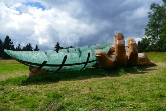 Auf einer Wiese ist aus Holz eine große Hand geschnitzt die das gläserne Arche-Schiff schützend festhält.