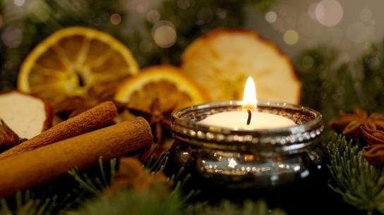 Ein Kerzenlicht im Tannengrün, weihnachtlich dekoriert.