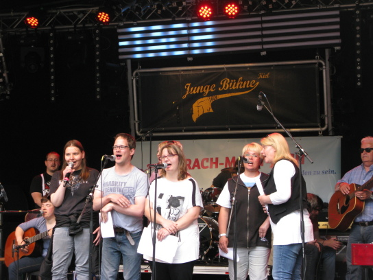 Fünf junge Menschen stehen auf einer Bühne vor M