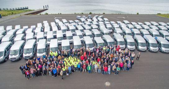 Zahlreiche Fahrzeuge und Menschen von oben fotografiert, im Hintergrund die Ostsee und grauer Himmel