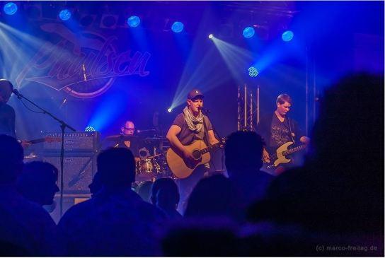 Ein junger Mann mit Gitarre auf einer Bühne