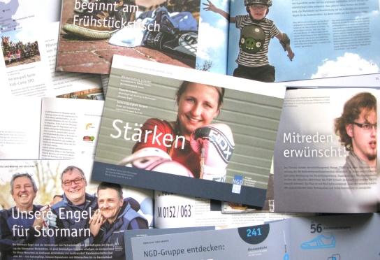 Viele aufgeschlagene Seite übereinandergelegt, in der Mitte der Titel des aktuellen Jahresberichtes mit der Überschrift Stärken und einem lächelnden Mädchen mit Boxhandschuhen darauf