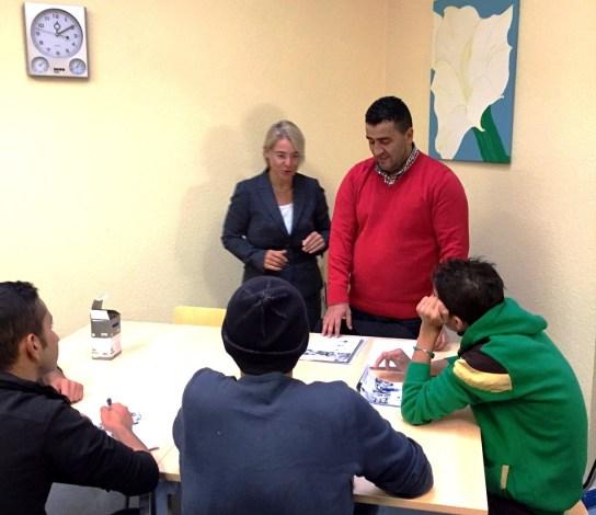 Eine Frau, Sozialministerin Alheit, schaut zu, wie ein Mann drei Jugendliche, die vor ihm sitzen, unterrichtet