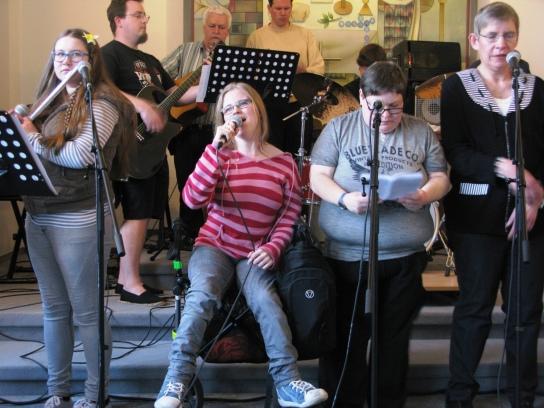 Eine Gruppe von Frauen singt, eine der Frauen spie