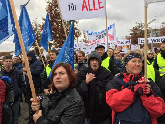 Menschen mit Spruchbändern und Fahnen ziehen durch eine Straße in Berlin