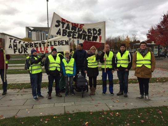 Eine Gruppe von Menschen in gelben Warnwesten und einem Transparent mit der Aufschrift: Keine Standards senken!