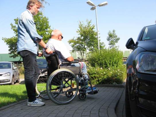 Ein Mann schiebt einen anderen Mann im Rollstuhl Richtung Fahrzeug