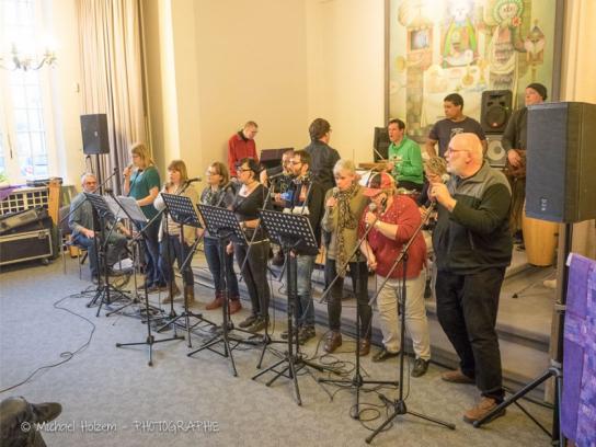 Viele Menschen auf einer kleinen Bühne singen und spielen Instrumente