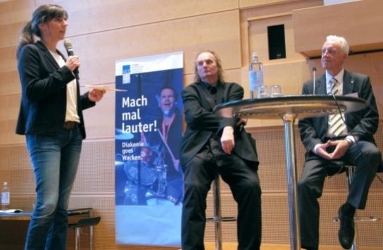 Ein Frau mit Mikrofon und zwei Männer auf einer B