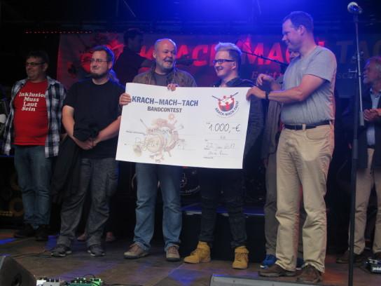 Vier Männer auf einer Bühne mit einem großen Scheck