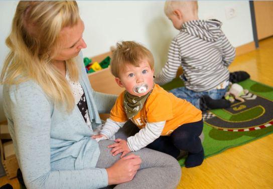 Eine Frau und ein Kleinkind mit Schnuller auf dem Boden sitzend, sie achtet auf das Kind