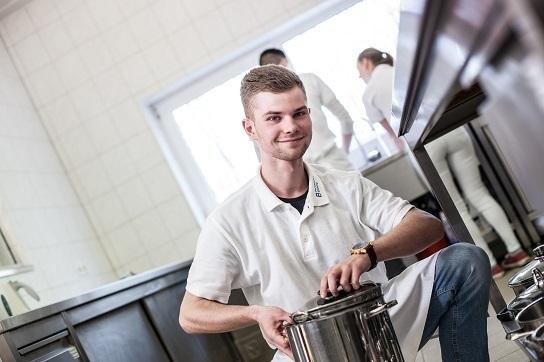 Bild: Ein junger Mann hält einen großen Kochtopf in der Hand. Er lächelt in die Kamera.