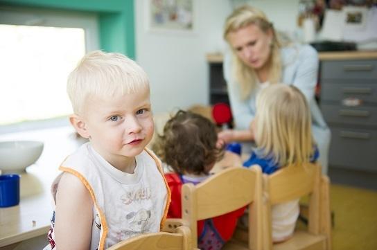 Bild: Ein kleiner Junge sitzt mit zwei anderen Kindern an einem Tisch. Er schaut keck in die Kamera.