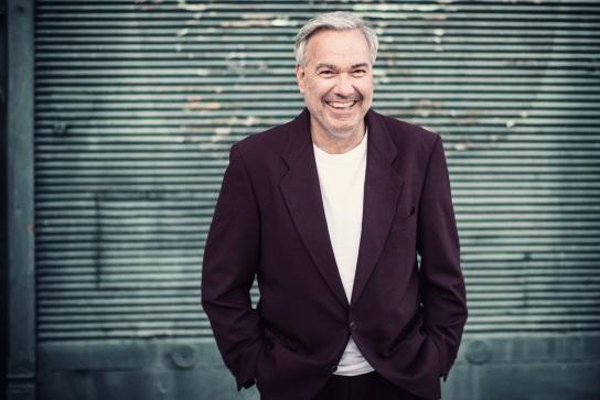 Bild: Ein Mann in Anzugjacke steht locker an einer Wand. Er lacht herzlich.