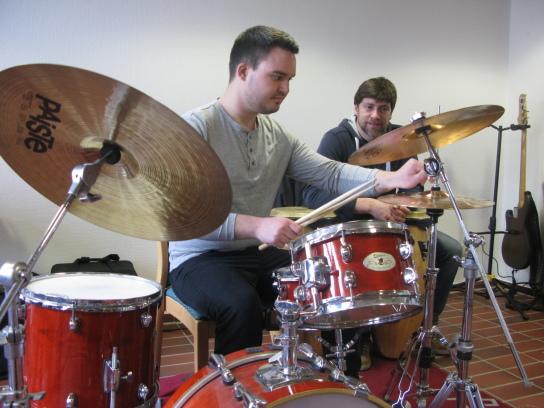 Ein junger Mann am Schlagzeug, im Hingrund ein Man