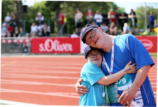 Bild: Zwei Menschen stehen vor einer Laufstrecke und umarmen sich.