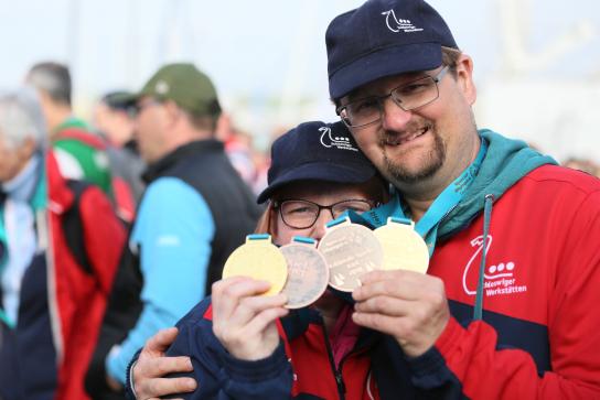 Bild: Zwei Menschen stehen nebeneinander und halten Goldmedaillen und Silbermedaillen hoch.