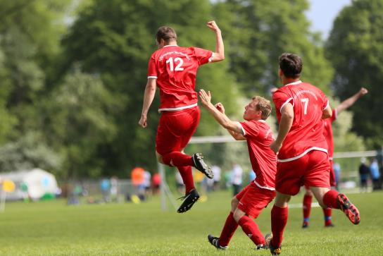 Bild: Drei Männer in roten Trikots spielen Fußball. Ein Mann ist in der Luft, mitten im Sprung.