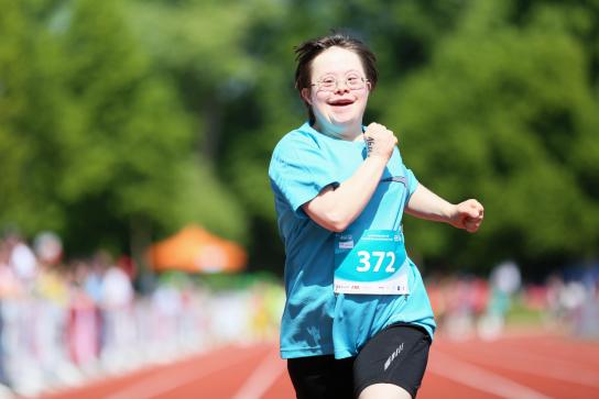 Bild: Eine Frau läuft mit einem Lächeln im Gesicht.
