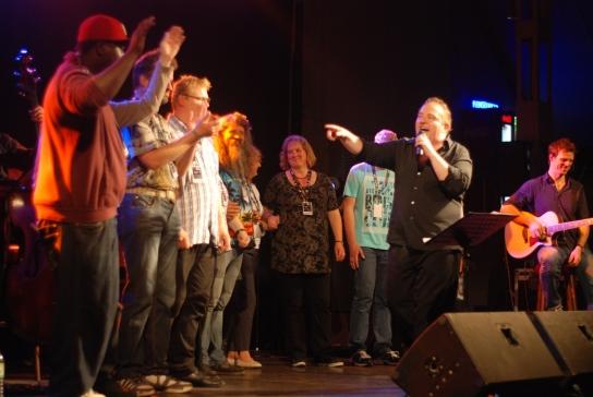 Bild: Eine Gruppe an Menschen steht im Halbkreis und tanzt. Gustav Peter Wöhler steht mit Mikrofon vor den Menschen und singt.