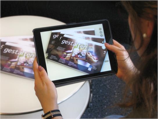 Bild: Eine Frau fotografiert mit einem Tablet drei Jahresberichte 2017 der NGD-Gruppe, die auf einem Tisch liegen.