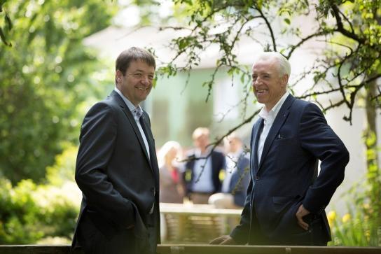 Bild: Zwei Männer in Anzug stehen sich gegenüber und lächeln.