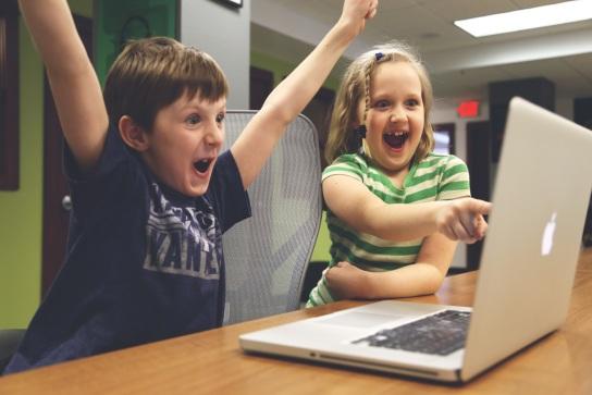Zwei Kinder, die mit Begeisterung vor einem aufgeklappten MacBook sitzen