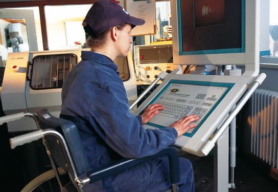 Junger Mann im Rollstuhl sitzt vor einer Maschinensteuerung