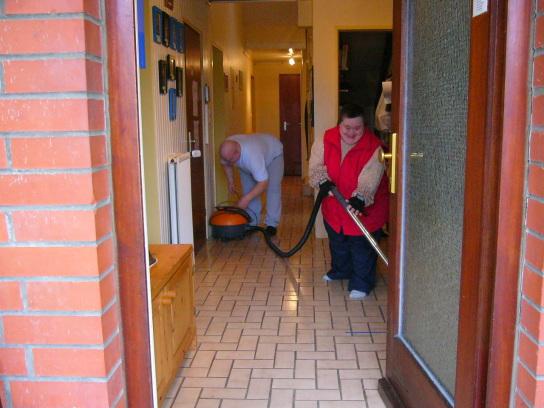 Zwei Bewohner beim Säubern des Hausflures.