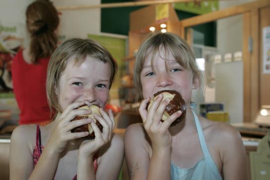 zwei junge Mädchen essen Laugenbrötchen aus ökologischer Herstellung