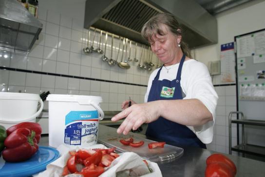 eine Mitarbeiterin schneidet Tomaten für den Rohkostsalat