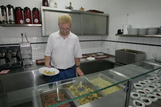 ein Mitarbeiter gibt das Mittagessen aus