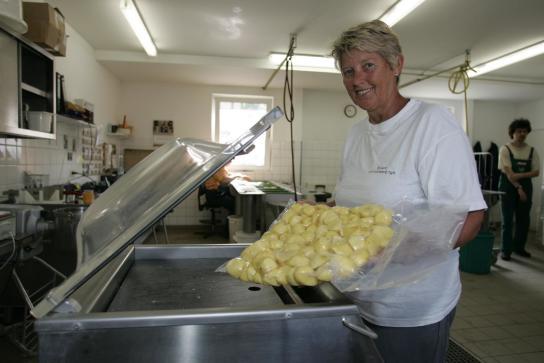 eine Mitarbeiterin vacuumiert frisch geschälte Kartoffeln ein