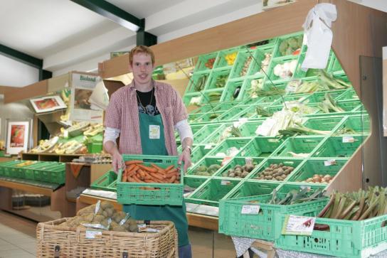 Ein Mitarbeiter bringt frische Möhren zum Gemüseregal