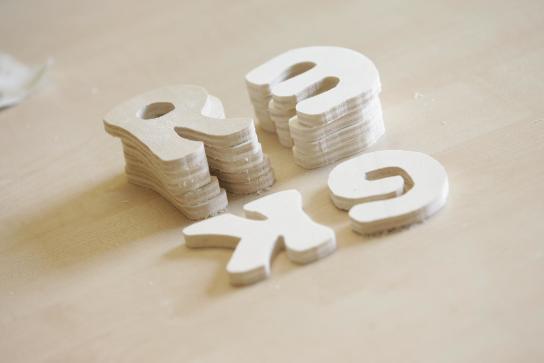 auf dem Tisch liegen 4 Stapel von Holzbuchstaben-Rohlingen
