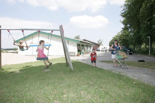 schaukelnde Kinder auf dem Spielplatz hinter dem Hofladen