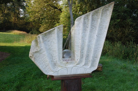 Sie sehen einen 88 cm hohen Engel aus Carrara Marmor. In seiner Mitte ist eine Glaskugel eingefasst.