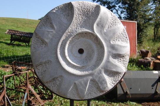Sie sehen ein Sonnenrad, das mit Stahlfuß 185 cm hoch ist. Es besteht aus Marmor.