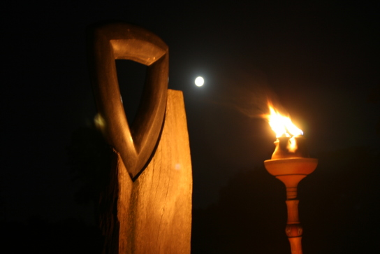 Eine Holz-/Steinskulptur wird bei Dunkelheit von einer Fackel angeleuchtet.
