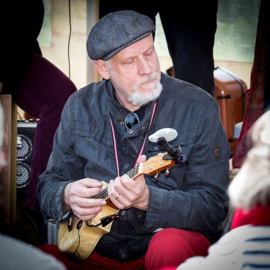 Ein Musiker spielt sitzend eine Ukulele.