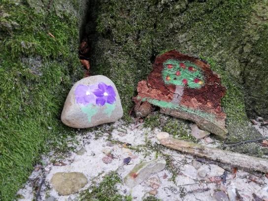 ein bemalter Stein und eine bemalte Baumrinde