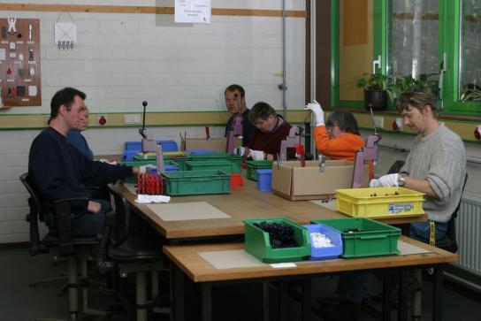 Eine Gruppe von Mitarbeitern stellt aus mehreren Einzelteilen ein gebrauchsfertiges Produkt her