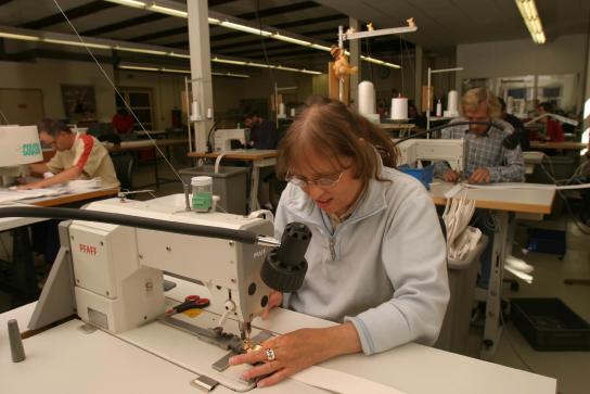 mehrere Mitarbeiter arbeiten an Nähmaschinen